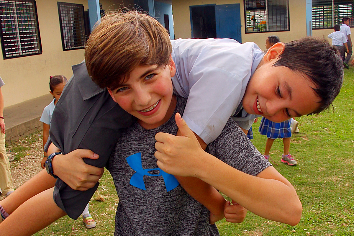 Landon boy carries another Landon boy on a field trip to Belize