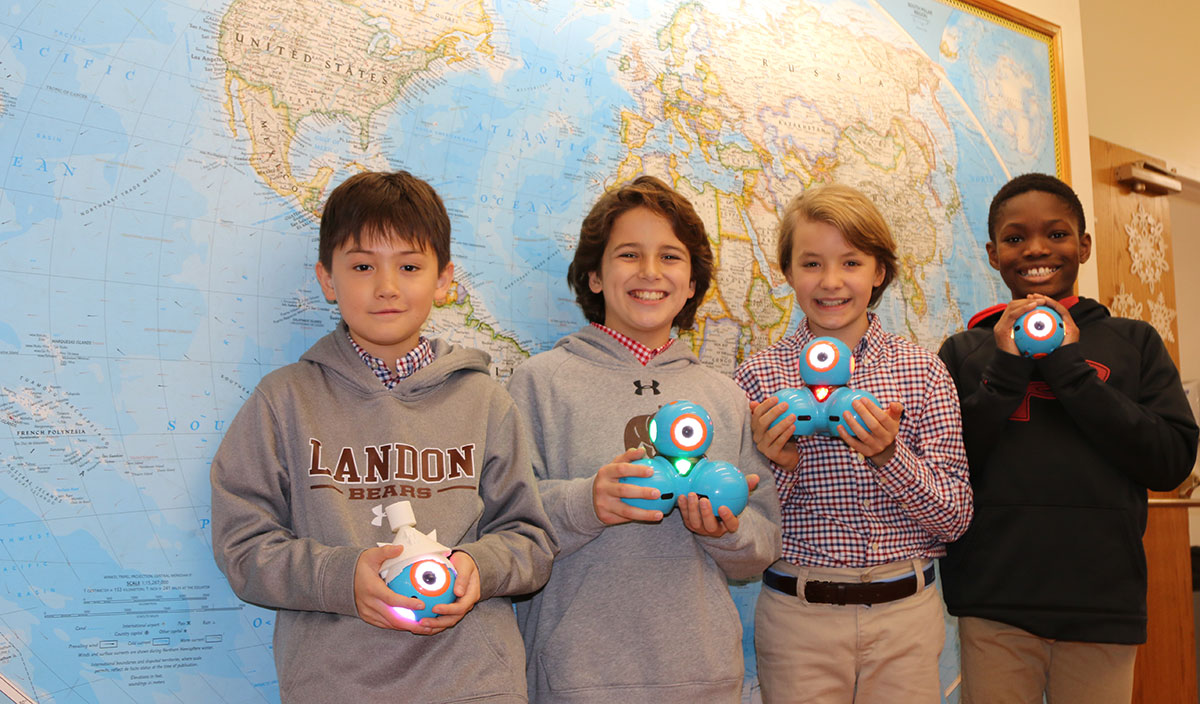 Four Landon Lower School students with programable robots