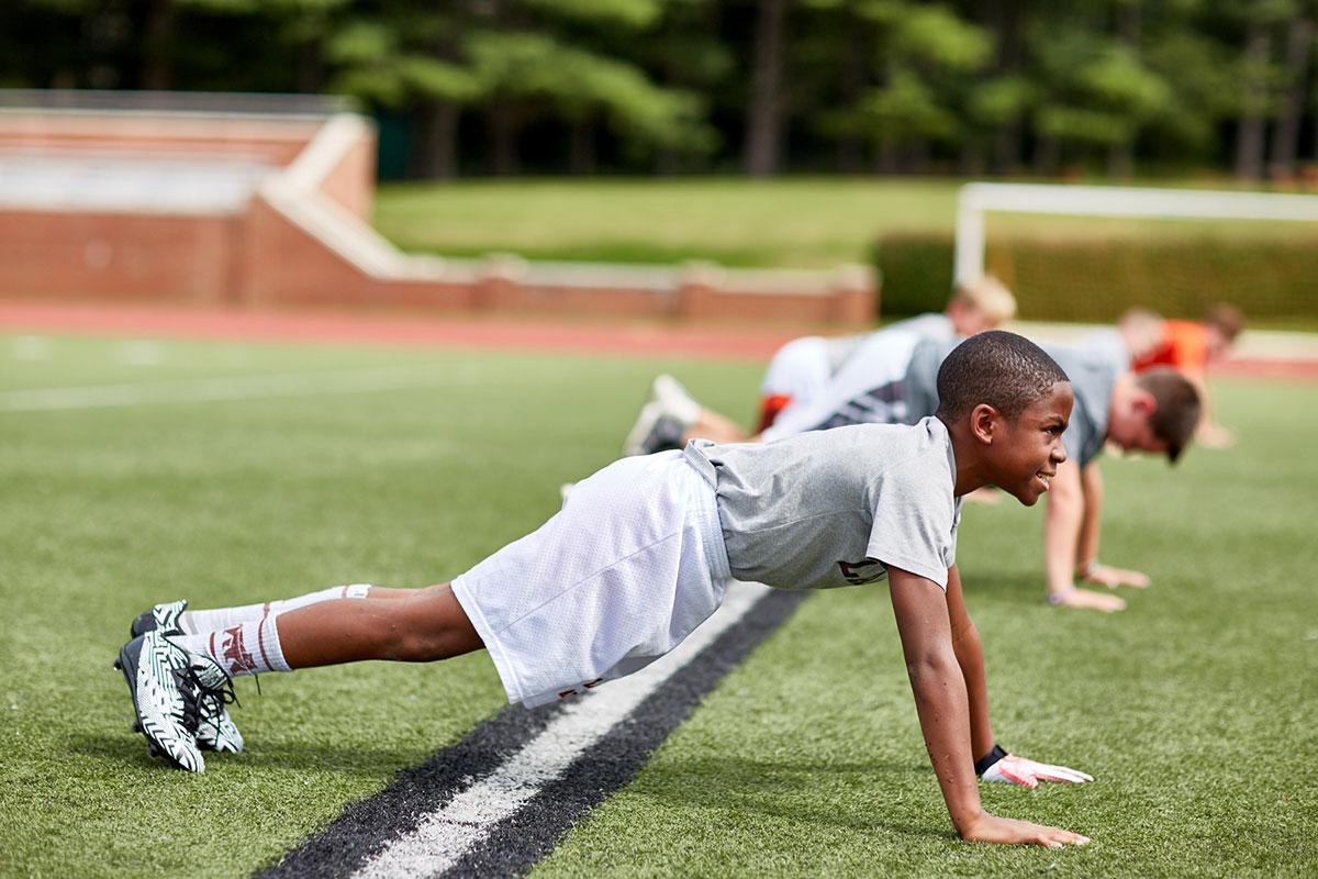 Landon Lower School boys working hard doing push ups on the sports field